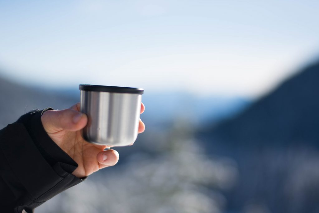Woman holding cup of coffee with mountains in background, Sasquatch