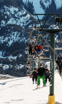 Green chairlift with guests on it at Sasquatch Mountain