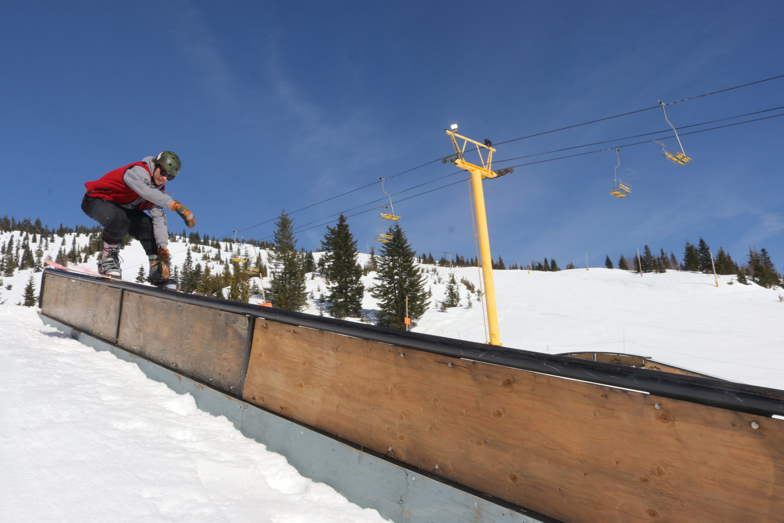 A man on a snowboard hitting a rail in Whistle Park at Sasquatch Mountain