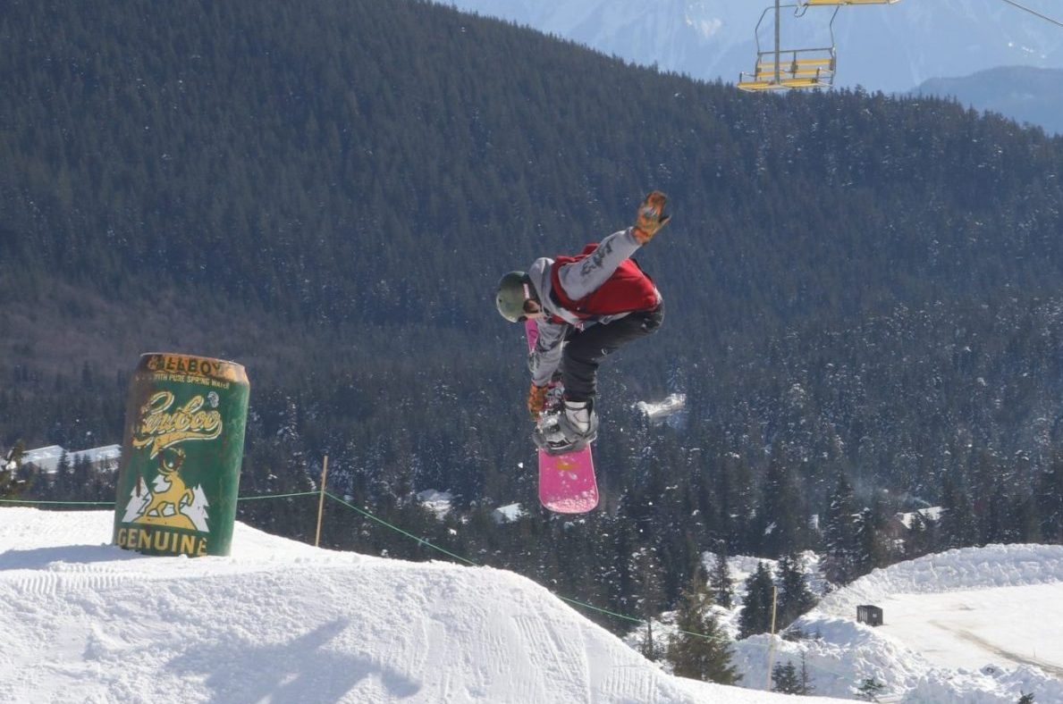 Snowboarder hitting a jump with feature nearby in a terrain park at Sasquatch Mountain