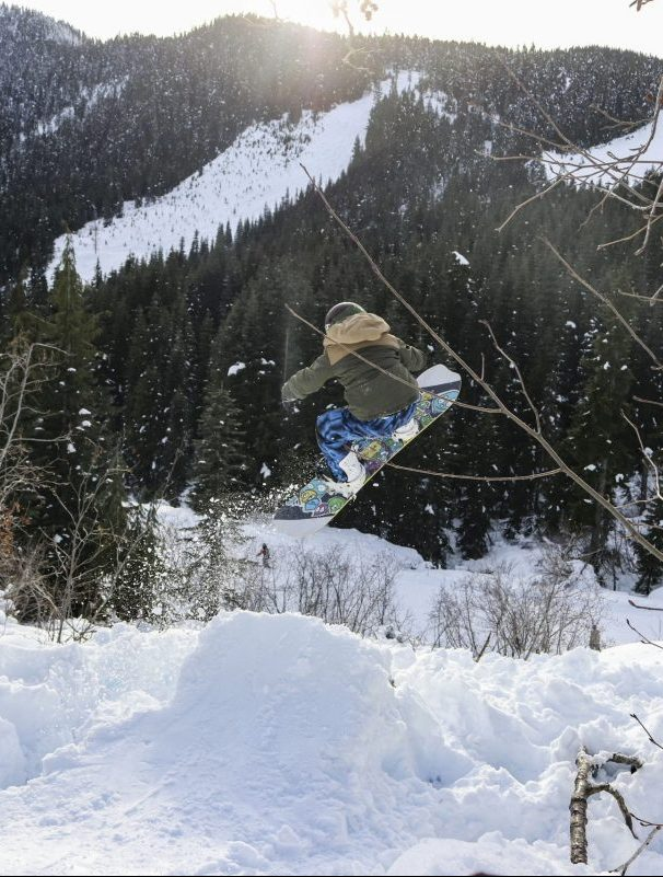 Little boy on a snowboard hitting a jump at Sasquatch Mountain