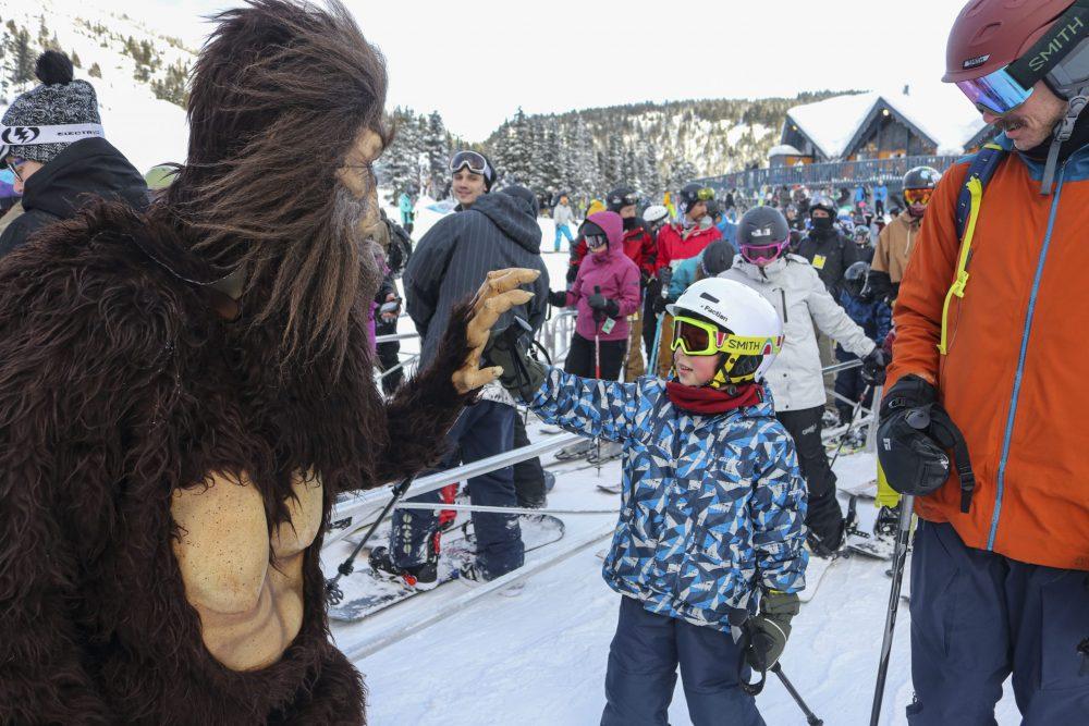 Sasquatch giving little boy high five in lift line at Sasquatch Mountain