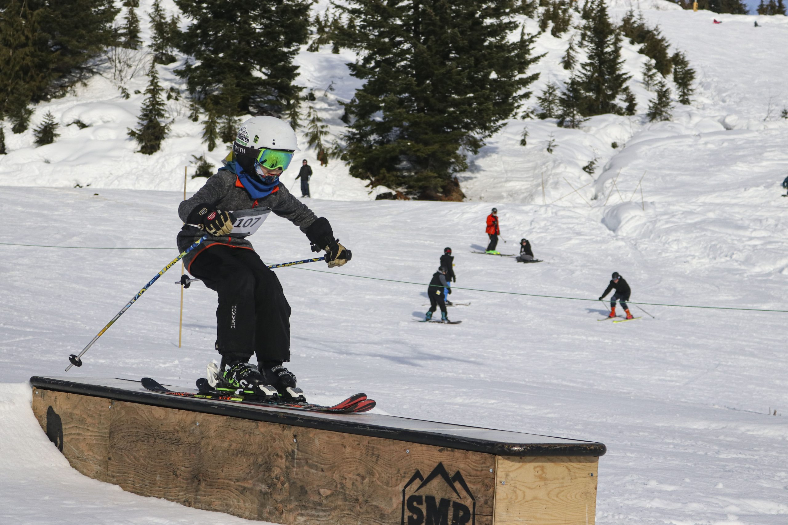 Young skier hitting a box rail in one of the terrain parks at Sasquatch Mountain