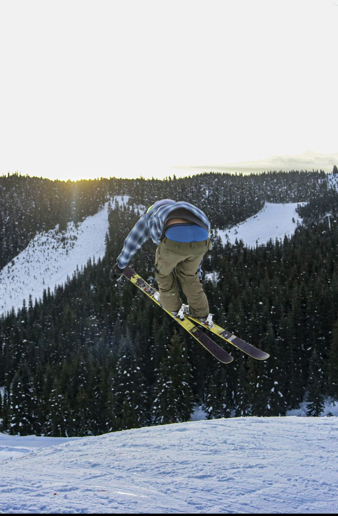 Skier going over a jump in one of the Sasquatch Mountain terrain parks