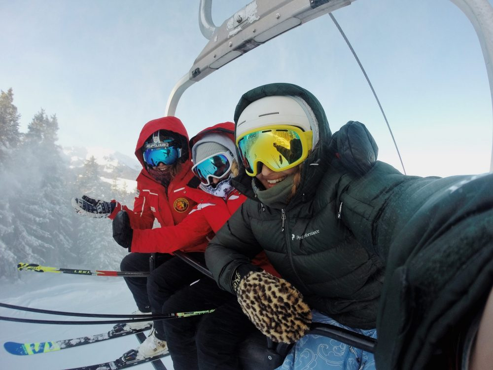 People enjoying skiing and snowboarding, chair ride